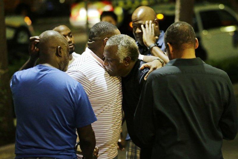 查爾斯頓(Charleston)17日晚間驚傳槍擊案,民眾相擁哀悼。(美聯社)
