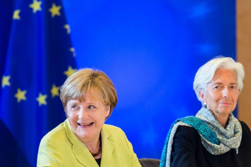 IMF總裁拉加德(右)與德國總理梅克爾(美聯社)