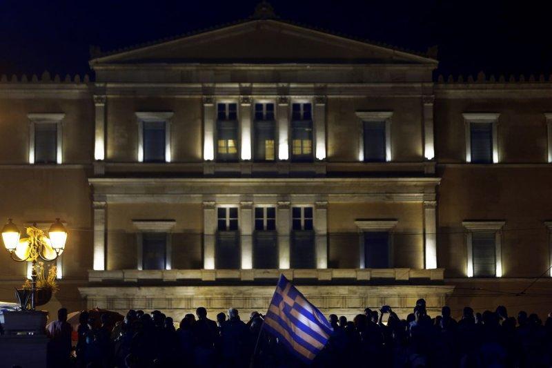 希臘支持政府、反對現行紓困計劃的民眾,29日晚間聚集在國會外面。(美聯社)
