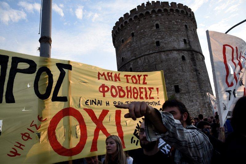 希臘民眾拉著寫上希臘文OXI(不)的抗議布條,堅決反對國際債權人提出的撙節方案。(美聯社)