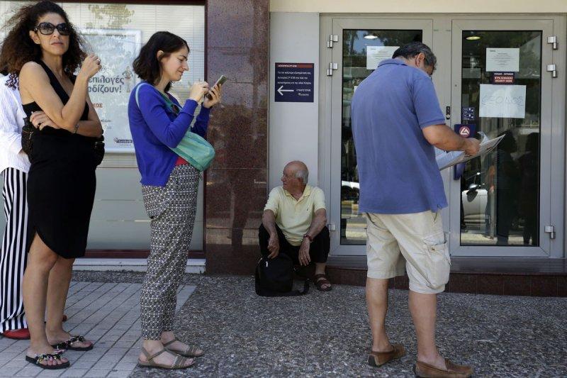 希臘實施嚴格的資本管制,民眾在提款機前方大排長龍。(美聯社)