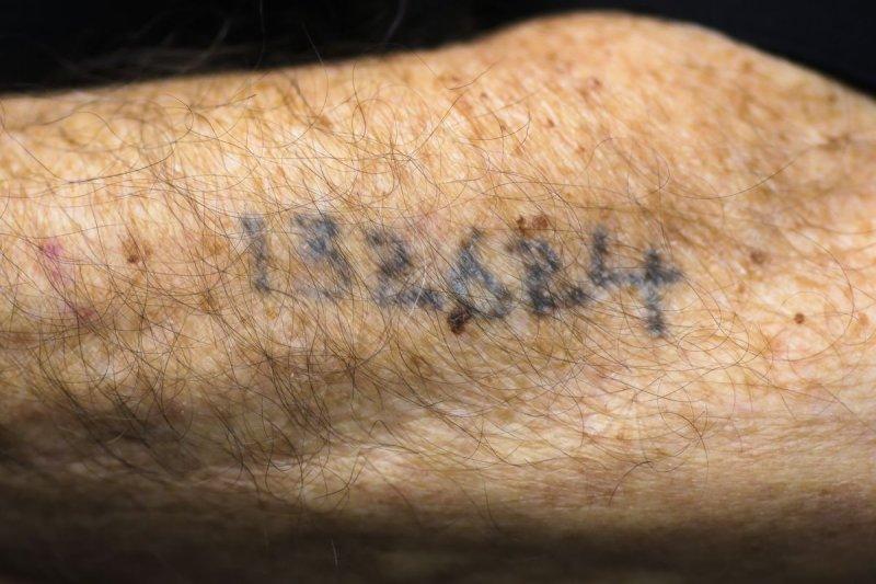奧斯維辛死亡集中營倖存者,手臂上留著當年的囚犯編號。(美聯社)