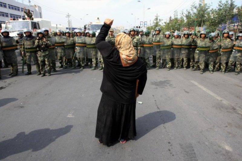 2009年中國鎮壓新疆,一名維吾爾族的女子站在中國鎮壓警方面前 (圖片來源:REUTERS)