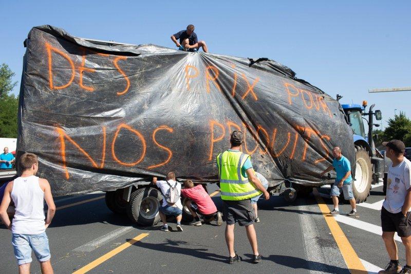 法國農民23日拉起大型布條抗議。(美聯社)