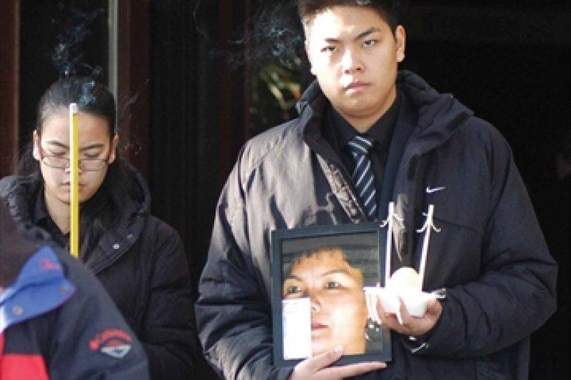 珍妮佛潘(左)在母親出殯時拿香祭拜。
