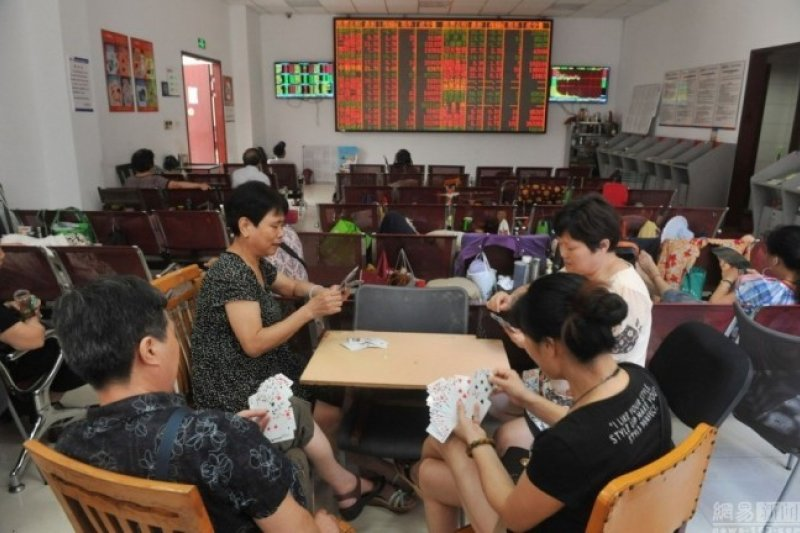 浙江杭州幾名股民在證券交易大廳內打撲克消遣。(取自網路)