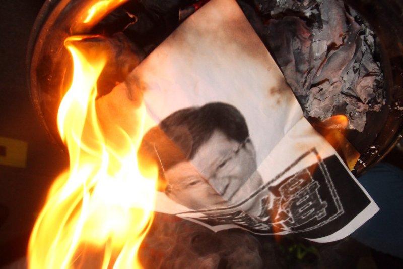 反黑箱課綱學生焚燒吳思華海報。(曾原信攝)