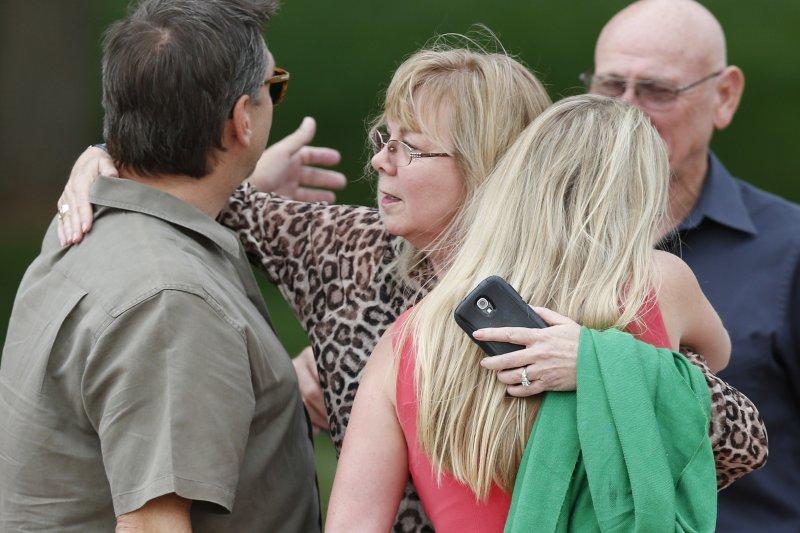 科羅拉多州槍擊案的受害者家屬,在法庭外互相安慰。(美聯社)