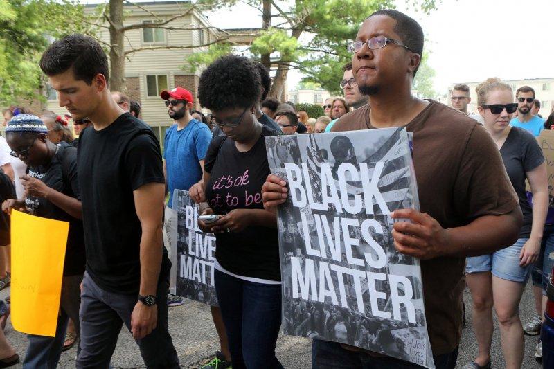 佛格森事件1周年,悼念者手持標語「黑人生命也重要」(美聯社)