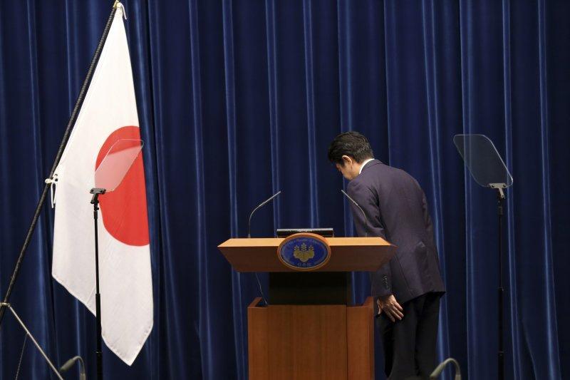 日本首相安倍晉三14日在記者會上向日本國旗鞠躬(美聯社)