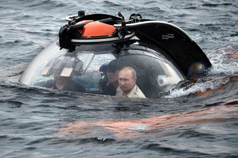 快要沒入海中了,普京不忘盯著鏡頭看(美聯社)。