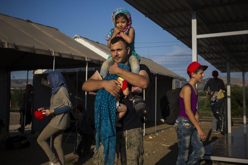 在馬其頓準備搭乘火車的一位敘利亞難民爸爸,背上懷裡都是自己的心肝骨肉。(美聯社)