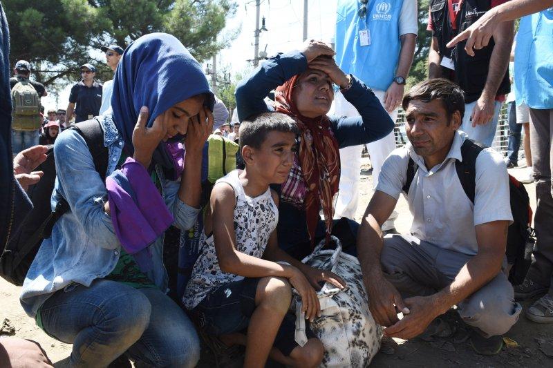 在希臘境內等候的難民家庭,臉上寫的全是愁苦悲戚。(美聯社)
