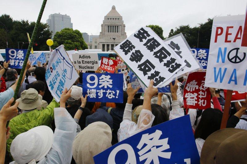 日本民眾冒雨包圍國會,反對新安保法案。(美聯社)