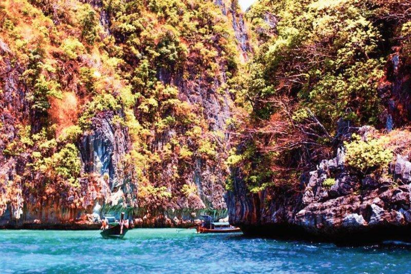乘著居民的小船,沿著溪流穿梭在 Koh Ha Yai 高聳的山壁間。