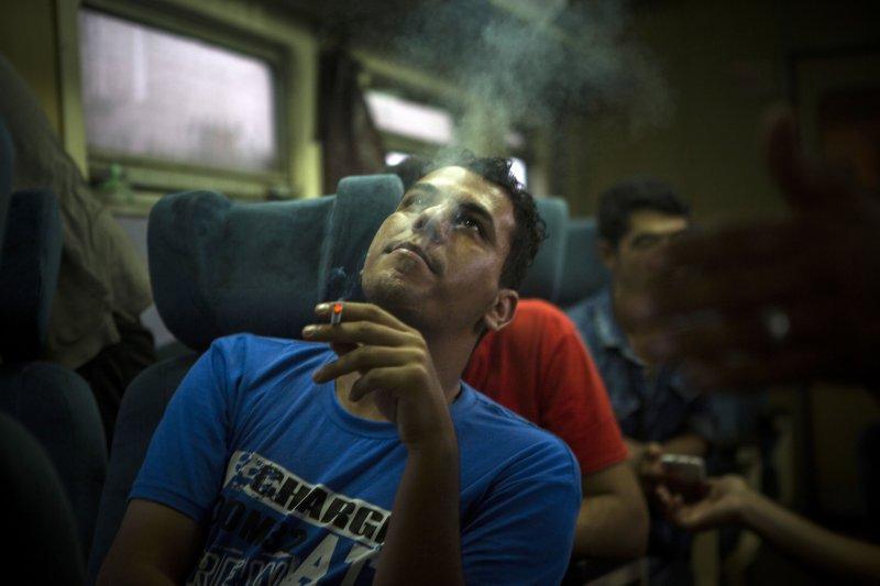 一名在塞爾維亞搭上火車的敘利亞難民,在座位上吞吐著鄉愁。(美聯社)