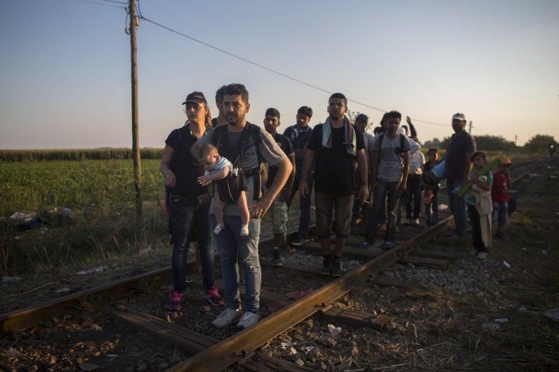 從塞爾維亞沿著鐵軌走進匈牙利國境的難民。(美聯社)