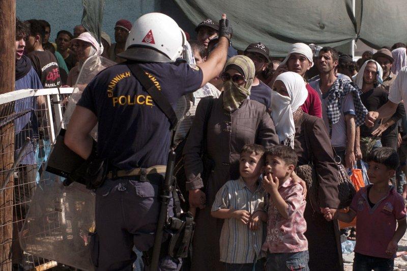希臘警方要求難民維持秩序,2名孩童驚恐不已。(美聯社)