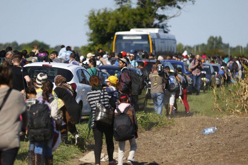 在匈牙利國境線上徒步行走的難民。(美聯社)