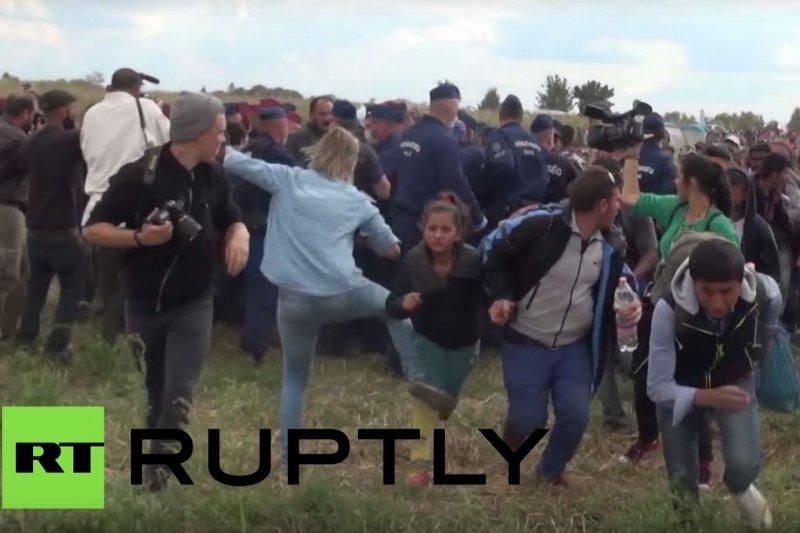拉斯洛偷偷出腳踢向難民。(YouTube)