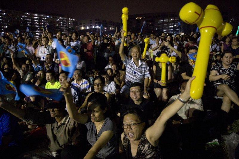 新加坡工人黨支持者高舉代表該黨的「黃色鐵錘」(美聯社)