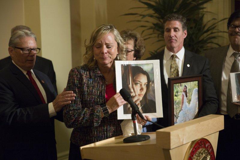 美國加州通過加工自殺合法化,梅納得的母親(持照片者)功勞甚大。(美聯社)