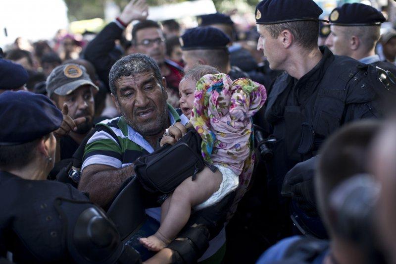 克羅埃西亞警察將難民集中於邊界區,小孩放聲大哭。(美聯社)