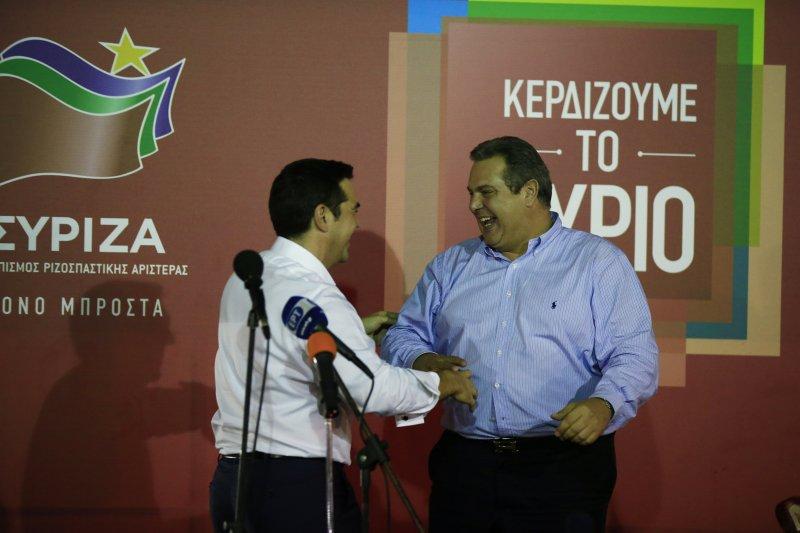 希臘激進左翼聯盟黨領導人齊普拉斯(左)在慶祝大會上與曾經聯合執政的獨立希臘人黨領導人坎梅諾斯握手(美聯社)