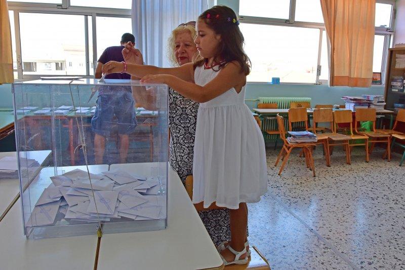 希臘國會選舉,小女孩替老奶奶投下神聖一票(美聯社)