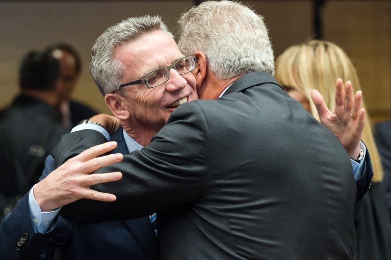 贊成配額制的一方大獲全勝,德國內政部長梅齊埃(Thomas de Maiziere)在會前擁抱歐盟官員。(美聯社)
