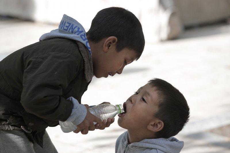 難民小孩在雅典(Athens)分水喝。(美聯社)