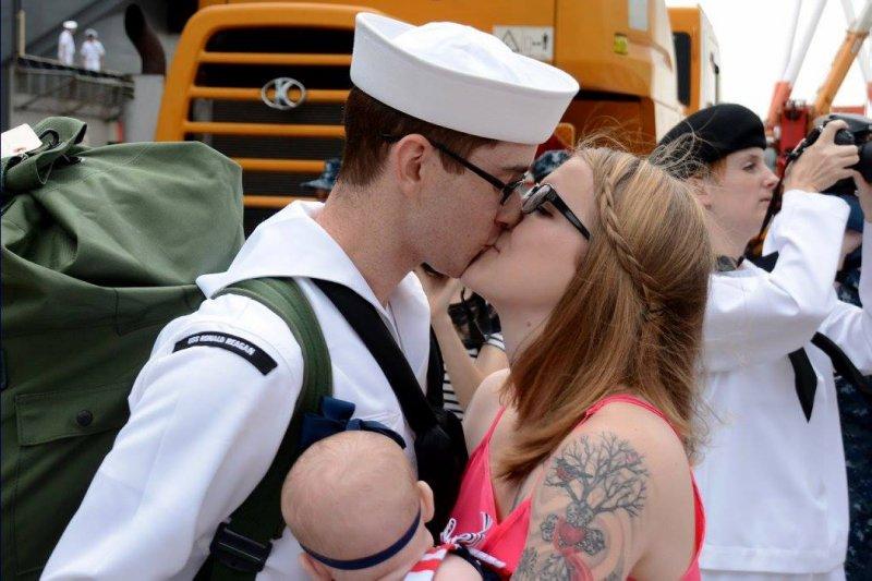 雷根號的水兵李吉(Stephen Ligget)在抵達橫須賀後,親吻自己的妻子。(美聯社)