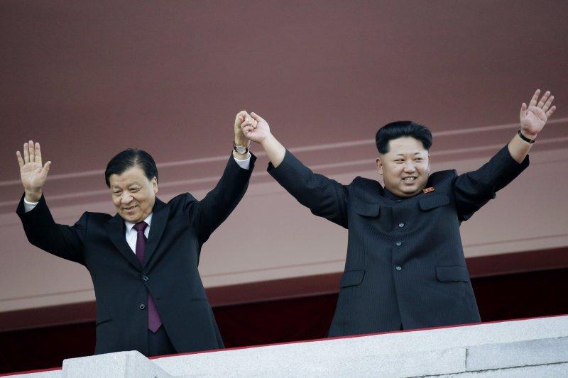 北韓最高領導人金正恩(右)去年10月10日在首都平壤主持大閱兵,牽起中國祝賀特使劉雲山的手接受歡呼。(美聯社)