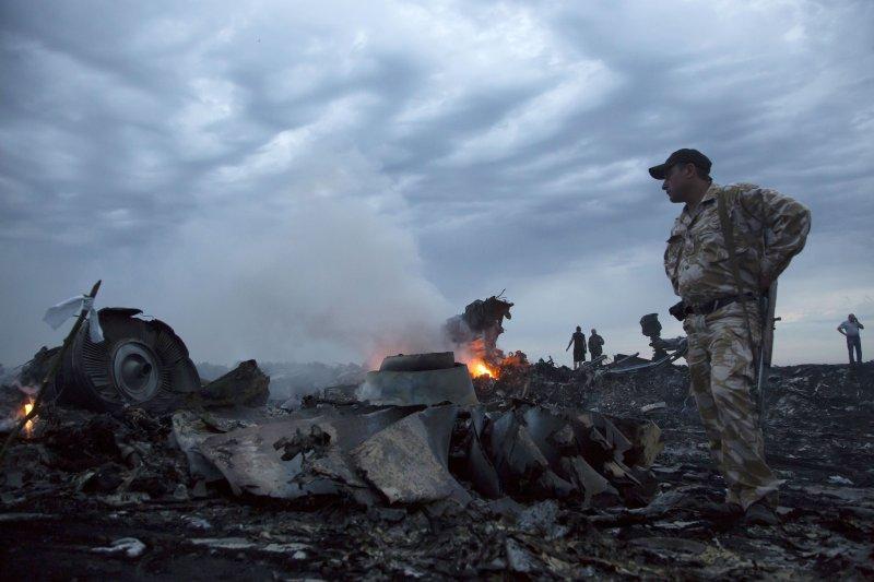 2014年7月17日,馬航編號MH-17班機在空中爆炸解體,殘骸散落滿地。(美聯社)