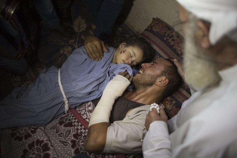 一名巴勒斯坦父親抱著自己死於以色列空襲的2歲女兒屍體痛哭,他懷有身孕的妻子也在這場空襲中喪命。(美聯社)