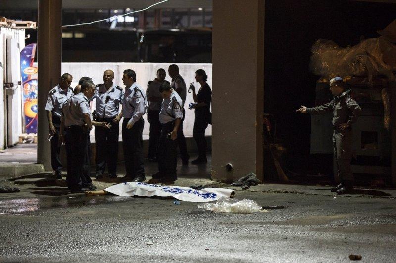 以色列警方與攻擊者遺體。(美聯社)