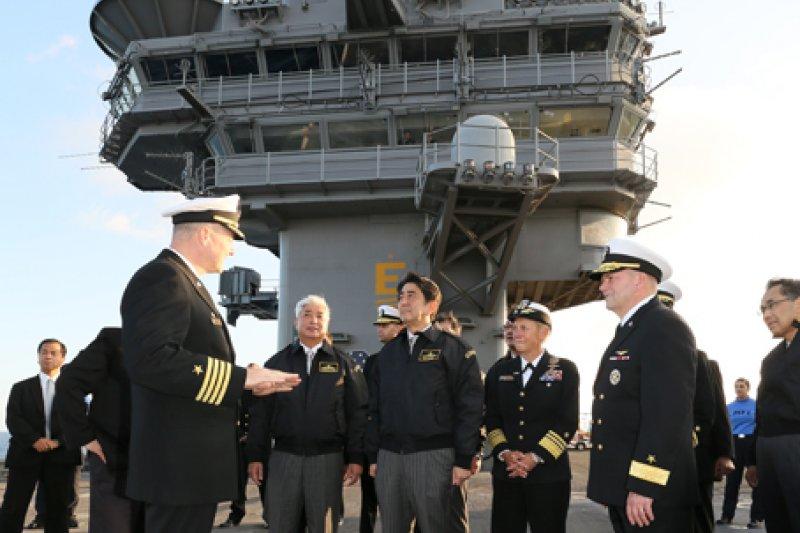 安倍晉三在雷根號航空母艦上與艦長交談。(翻攝首相官邸網站)