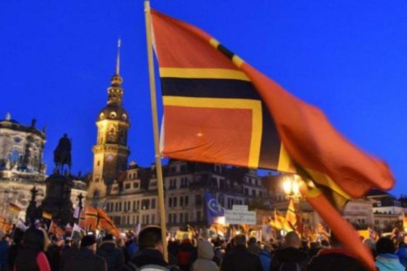 支持者的旗幟:用德國國旗的金紅黑三色畫成的基督教十字架。(BBC中文網)
