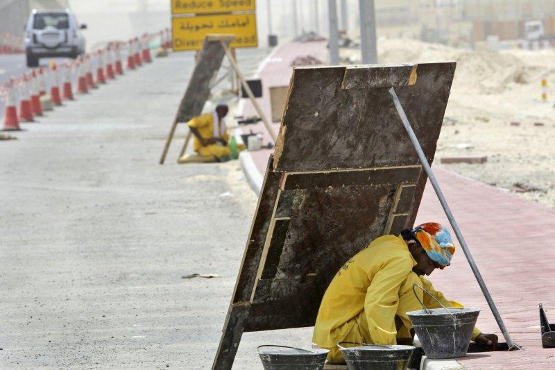 杜拜一名工人靠著木板遮陽(美聯社)