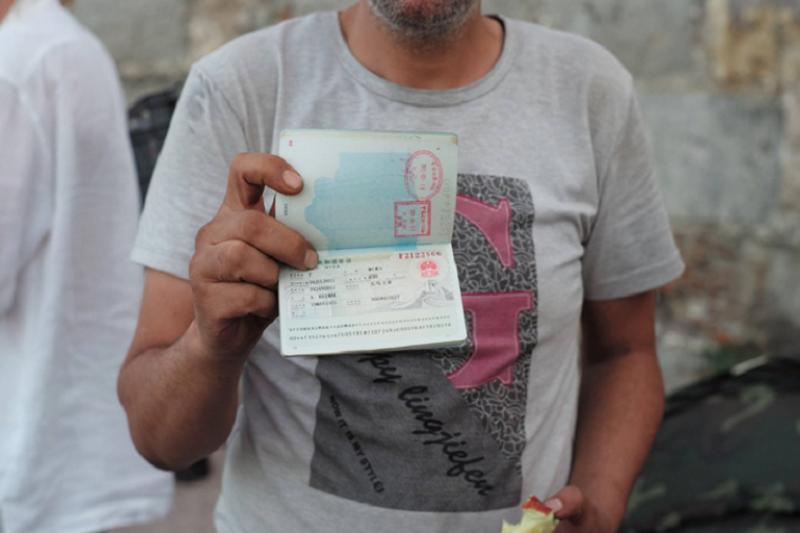 """在科斯島上岸的一位敘利亞難民展示護照上的舊中國簽証。 """"KOS REFUGEES NEED YOUR HELP"""" on Facebook(作者提供)"""