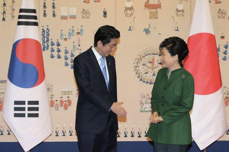 日本首相安倍晉三與南韓總統朴槿惠見面,安倍主動伸手示意。(美聯社)