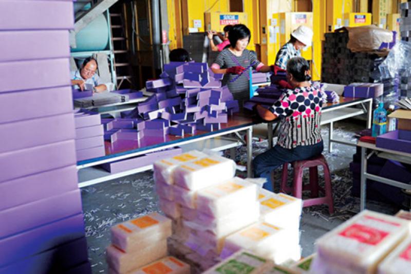 趕出口!10月23日,烏日農田邊的米加工廠,20多名員工趕著摺紙盒,真空包裝的新米,堆置角落;盒子上印著簡體字「天貓國際」,原來這些米,是要賣到中國去。(攝影程思迪)