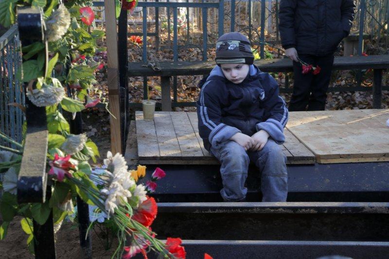 搭上俄羅斯失事航班的盧許申科(Nina Lushchenko),她的家人已經在家鄉大諾夫哥羅德市(Veliky Novgorod)附近的村莊為她舉行喪禮。盧許申科的孫兒5日在墓前思念祖母。(美聯社)