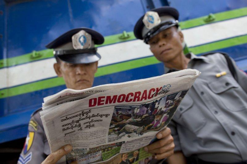 兩位緬甸警察一起閱讀一份名為《民主今日》(Democracy Today)的報紙。(美聯社)