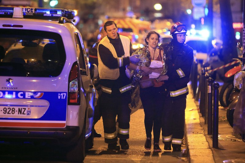 巴黎恐怖攻擊。救援人員協助一名女子離開事發現場。13日深夜,巴塔克蘭劇院(Bataclan)發生槍擊事件,恐怖份子一度挾持100多名人質,最後造成至少87人死亡。(美聯社)