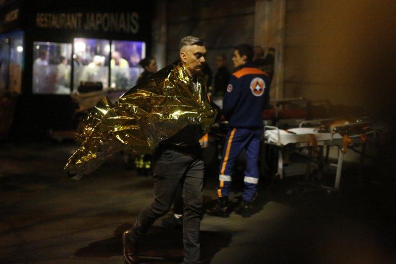 巴黎恐怖攻擊。一名幸運的生還者步出巴塔克蘭劇院(Bataclan)。13日晚間,巴黎巴塔克蘭劇院(Bataclan)發生槍擊,100多人遭恐怖份子挾持,最後造成87人死亡。(美聯社)