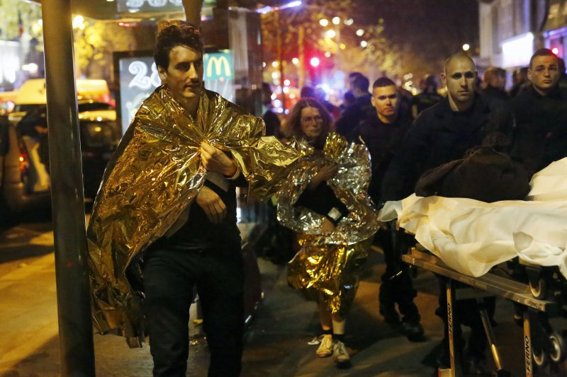巴黎恐怖攻擊。生還者紛紛步行離開巴塔克蘭劇院(Bataclan)。13日晚間,劇院發生槍擊事件,至少造成87人死亡。幾乎同時間,位於巴黎北郊聖丹尼(Saint-Denis)的法國國家體育場(Stade de France)也發生兩起自殺炸彈攻擊。(美聯社)