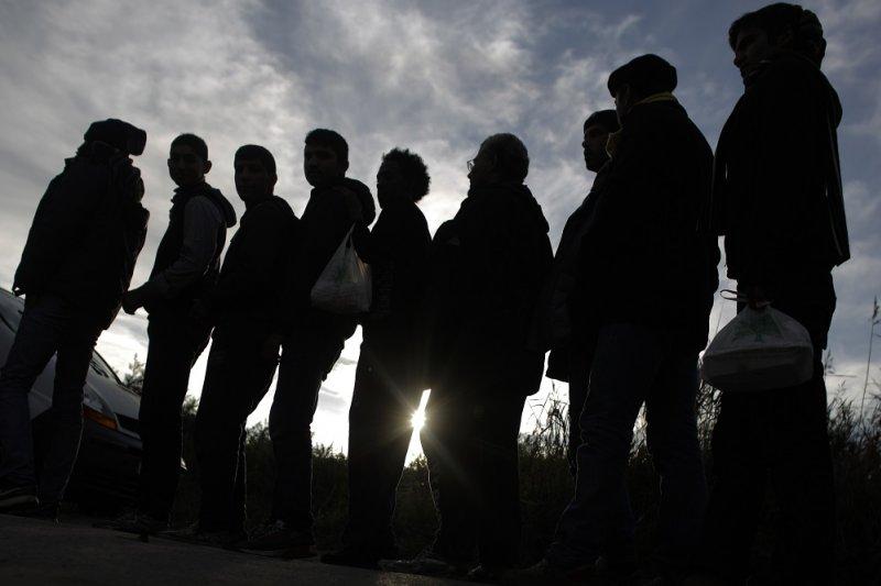於法國北部難民營排隊領取物資的難民(美聯社)