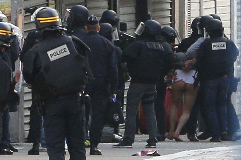 巴黎警方特種部隊在聖丹尼區圍捕恐攻主嫌,激烈駁火後逮捕一名嫌犯(右方未穿褲者)(美聯社)