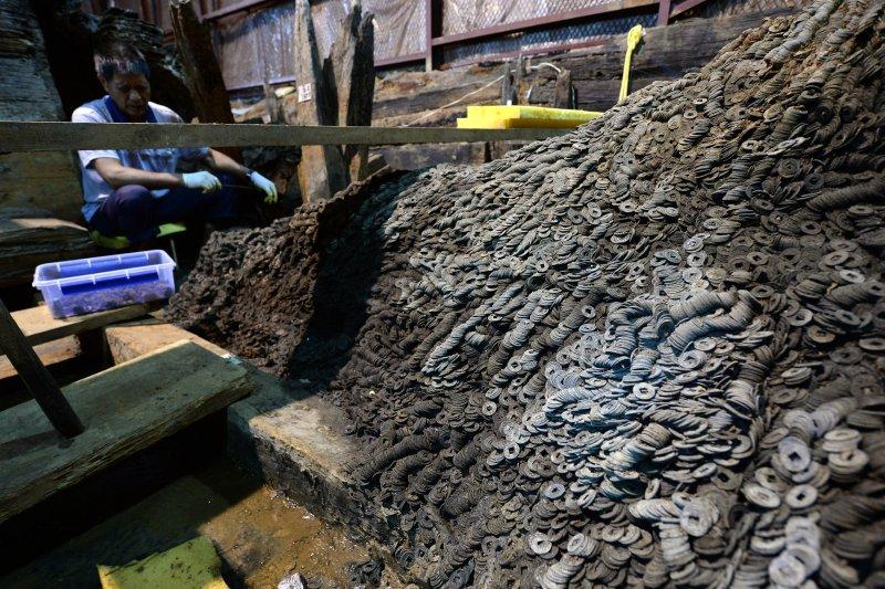 工作人員在海昏侯墓考古發掘現場清理五銖錢(新華社)